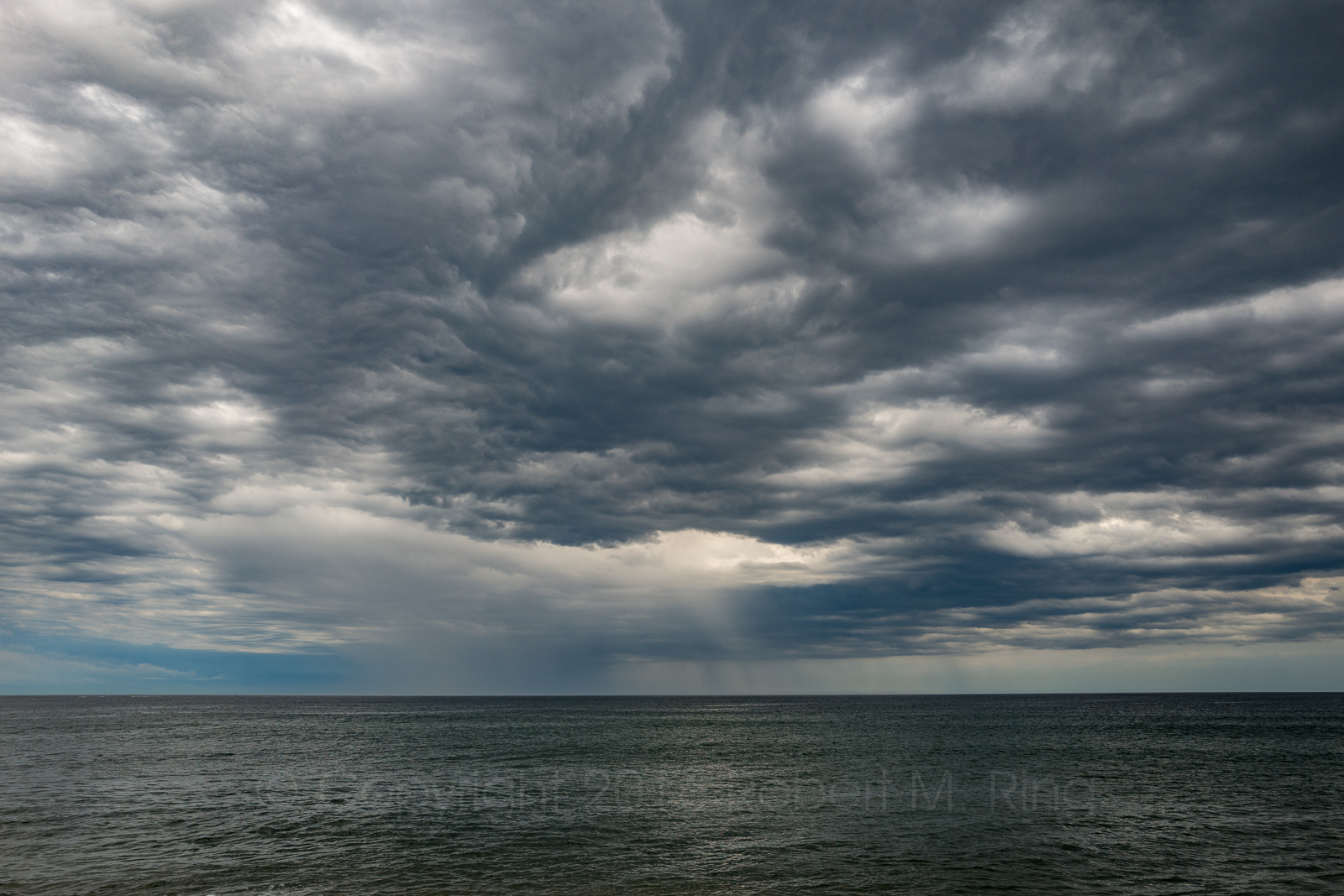 After a rain storm passes overhead heading eastward it can be seen here out to sea off of Plum Island on the coast of Massachusetts...