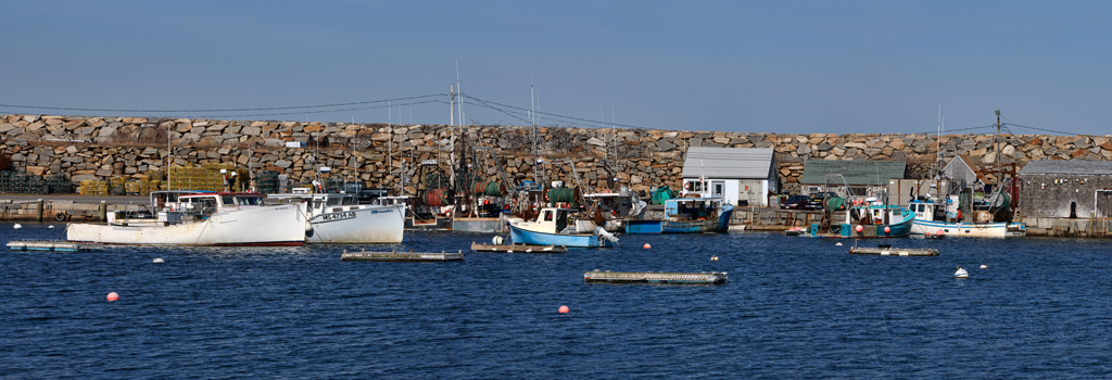 A very small 'working' harbor with a granite pier on one side.