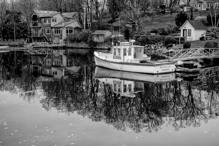Reflections of a lobster boat in Annisquam, MA.